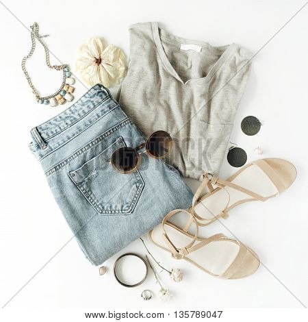 flat lay feminine clothes and accessories collage with shirt jeans shorts sunglasses bracelet sandals earrings on white background.