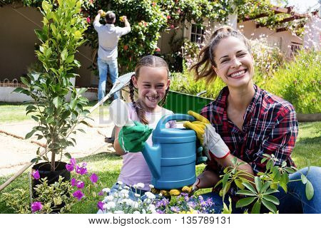 Mother and daughter holding a watering can while gardening in garden