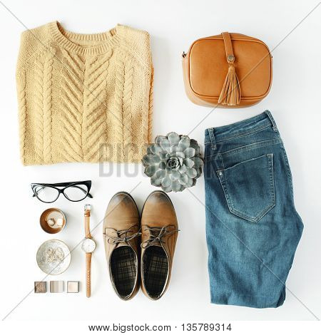 flat lay feminine clothes and accessories collage with brown cardigan jeans glasses watch earrings purse boots and succulent on white background.