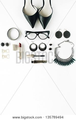 flat lay feminine accessories collage with glasses high heel shoes mascara lipstick bracelet earrings necklace and bow tie clips on white background.