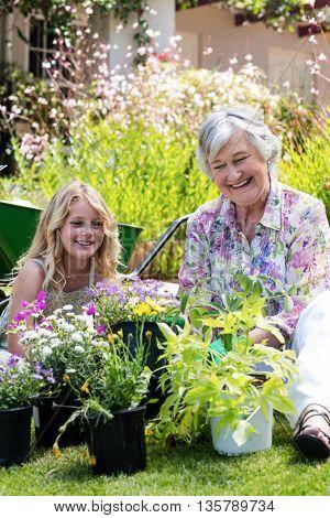 Grandmother and granddaughter gardening together in garden