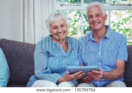 Portrait of smiling senior couple using digital tablet at home