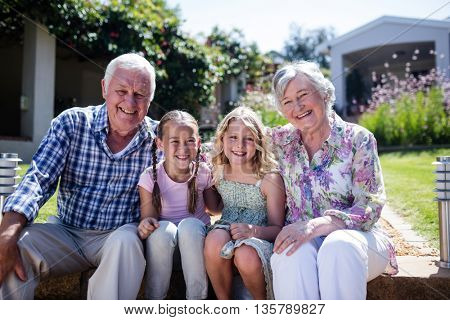 Grandparents and granddaughters sitting in the garden on a sunny day
