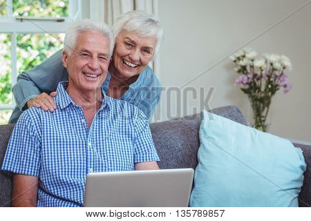 Portrait of smiling retired couple using laptop at home