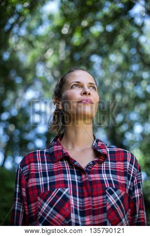 Thoughtful young woman looking up in back yard