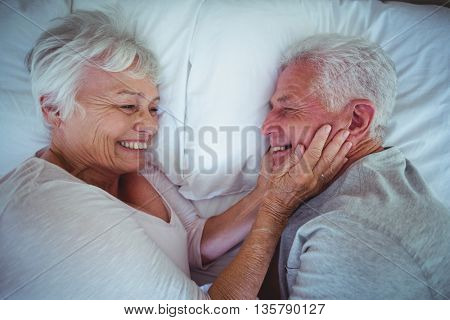 Senior woman holding husband cheeks while lying on bed in room