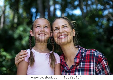 Cheerful mother with daughter looking up in back yard