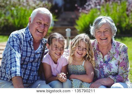 Portrait of cheerful girls with grandparents while sitting in back yard during sunny day