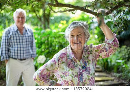Portrait of senior woman with husband standing in background at back yard