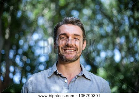 Portrait of happy young man while standing in back yard