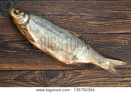 Salty dry fish for beer on a wooden background top view