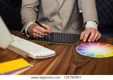 Creative businessman using graphic tablet in office