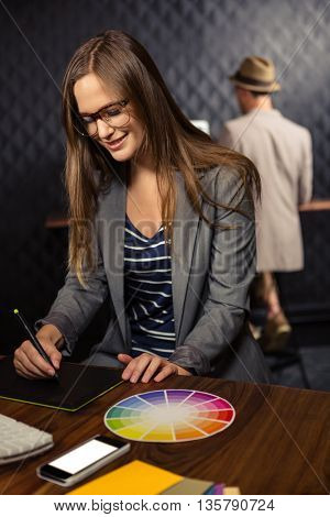 Creative businesswoman using graphic tablet in office