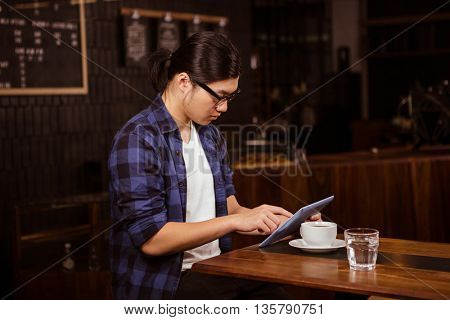 Hipster man using tablet in a coffee shop