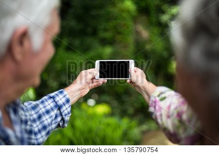 Senior couple taking selfie through smart phone in back yard