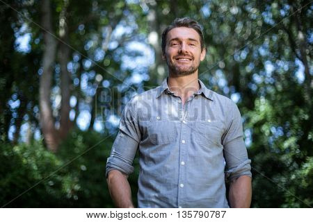Portrait of happy young man against trees in back yard