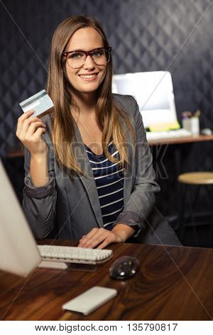 Creative businesswoman showing a credit card in office