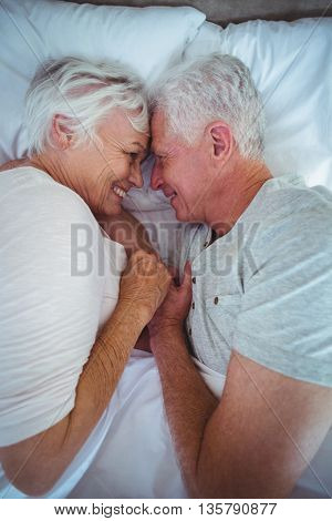 Overhead view of senior couple touching head while holding hands on bed in room