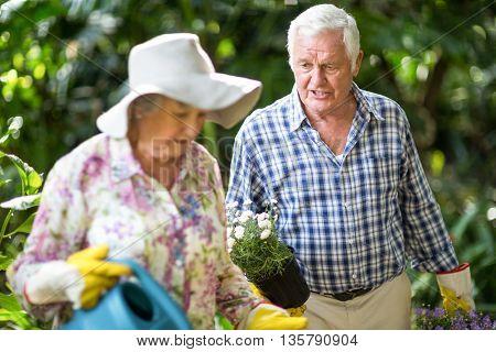 Senior man talking to wife while walking in garden