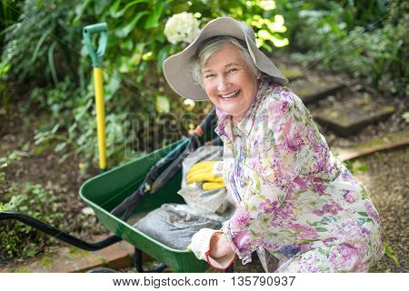 High angle view of happy senior woman with wheelbarrow in garden