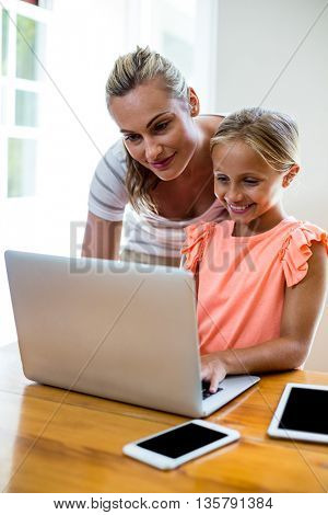 Close-up of mother assisting daughter in uising laptop at home