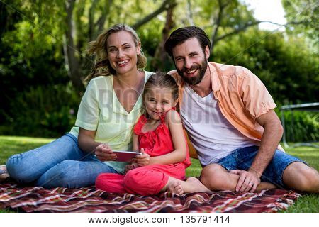 Portrait of smiling family with mobile phone sitting in yard