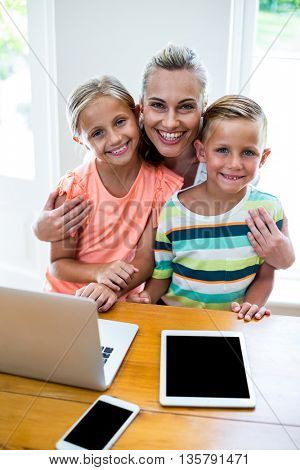 Portrait of happy mother with children using technologies at home