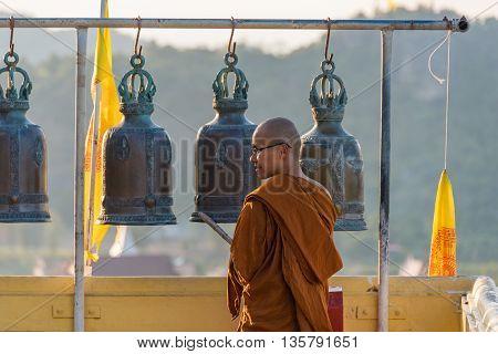 Hua Hin Thailand - Dec 26 2015: Buddhist monk apprentice with Buddhist bells on the background