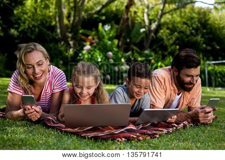 Close-up of family using technologies while lying at yard