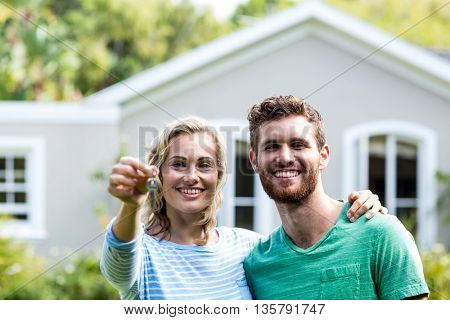 Portrait of smiling couple with keys standing against house