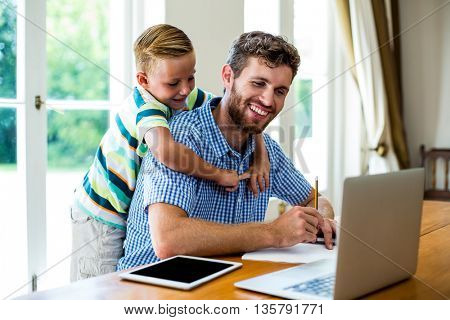 Happy father with son working by technologies at table in home