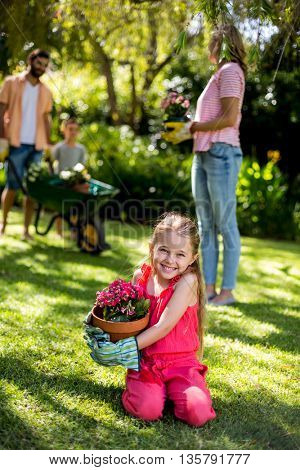 Smiling girl holding flower pot while family standing in background