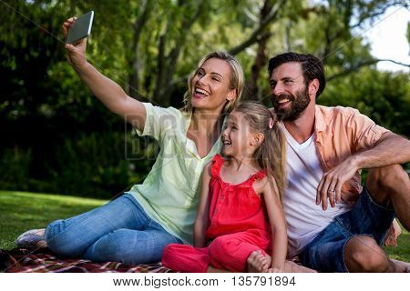 Smiling woman taking selfie with husband and daughter while sitting at yard