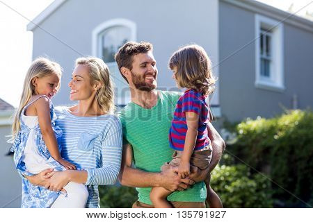 Happy parents carrying children in yard against house