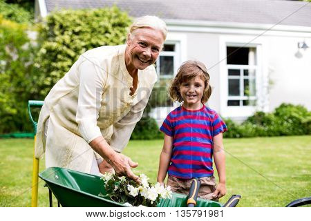 Garndmother and boy with flower pots in wheelbarrow at yard