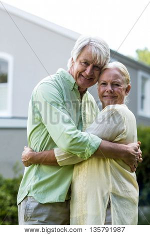 Portrait of smiling senior couple embracing against house