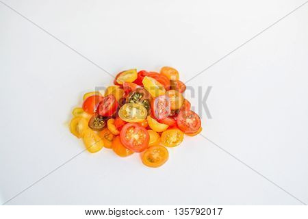 Different varieties of cherry tomatoes on white background