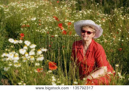 The elderly woman sitting in a meadow with poppies and chamomiles.