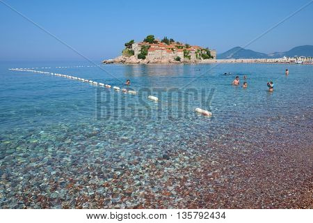 SVETI STEFAN, MONTENEGRO - JULY 08, 2015: shingle and clear sea of Sveti Stefan beach. The shot frames the landscape of sea and island of Sveti Stefan