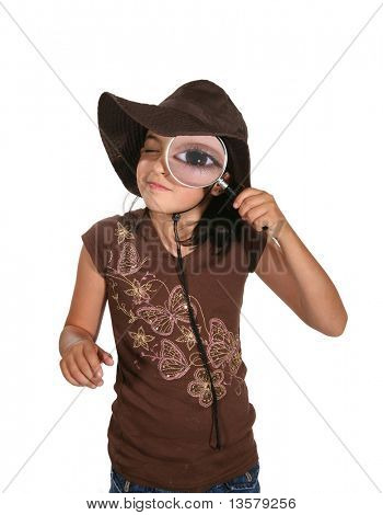 A girl looking into a magnifying glass