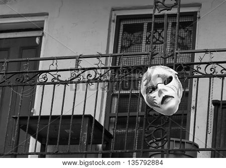NEW ORLEANS, USA - MAY 14, 2015: A carnival mask attached to a balcony in Bourbon Street in French Quarter. The picture is monochrome.