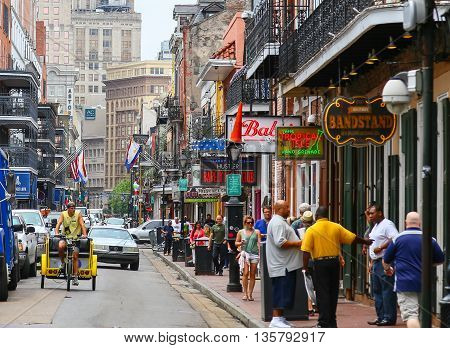 NEW ORLEANS, USA - MAY 14, 2015: Bourbon Street in French Quarter with many pedestrians and vehicles. There are a lot bars with neon signs in the back modern highrises.