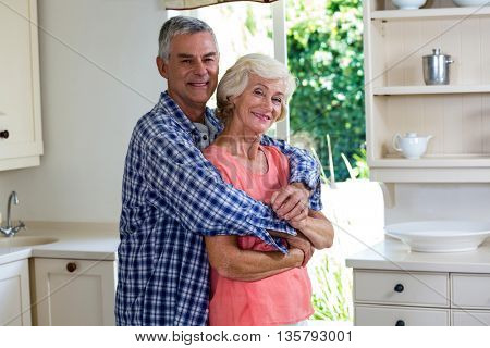 Portrait of smiling couple embracing in kitchen at home