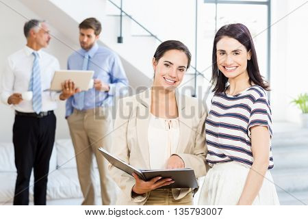 Businesswoman and a colleague smiling at camera while businessmen discussing in the background