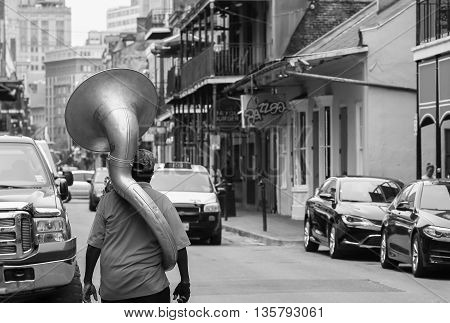 NEW ORLEANS, USA - MAY 14, 2015: A man with a sousaphone on his back walking down Bourbon Street in French Quarter. The picture is monochrome.