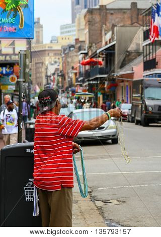 NEW ORLEANS, USA - MAY 14, 2015: Street vendor advertising colorful Mardi Gras beads on busy Bourbon Street in French Quarter.