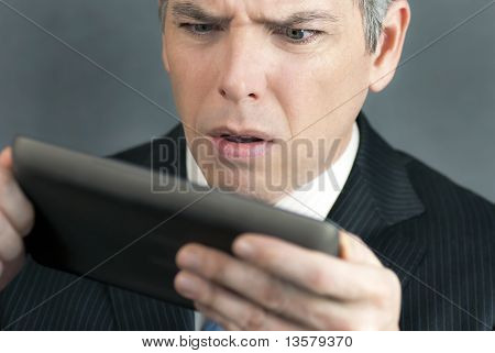Worried Businessman Looks At Tablet