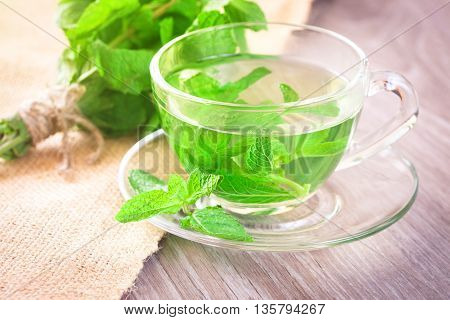 Cup of herbal mint tea on the table and a bunch of mint on the table