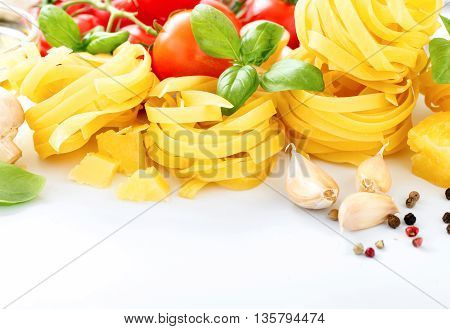 Closeup fettuccine with ingredients for cooking pasta on a white background