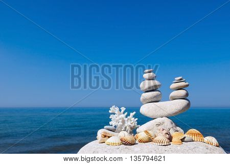 Concept of harmony and balance. Rock Zen of seashells on a background of summer sea